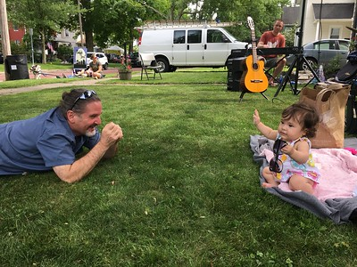 Adam Grom of Medina plays with his neighbor, 8-month-old Maylee Blower, as they listedn to the Wolfe Creeque Band on Saturday during Rockin' the Court. Maylee's dad, Elijah Blower, sings and plays guitar in the band, and Grom's son, Ben Grom, plays drums for them. BOB SANDRICK / GAZETTE