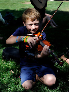 Sam Costantino, 8, plays his violin in the shade on Thursday, July 26, at the Rocky Grass Academy in Lyons. For more photos and video of the academy go to www.dailycamera.com Jeremy Papasso/ Camera