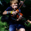 "Sam Costantino, 8, plays his violin in the shade on Thursday, July 26, at the Rocky Grass Academy in Lyons. For more photos and video of the academy go to  <a href=""http://www.dailycamera.com"">http://www.dailycamera.com</a><br /> Jeremy Papasso/ Camera"