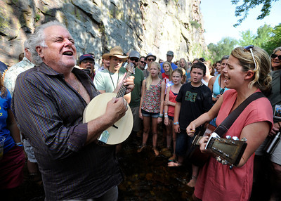 Award winning bluegrass musician Peter Rowan, left, christens a newly built banjo by playing it in the middle of the river with singing instructor Aoife O'Donovan, right, and the rest of the academy on Thursday, July 26, at the Rocky Grass Academy in Lyons. For more photos and video of the academy go to www.dailycamera.com Jeremy Papasso/ Camera
