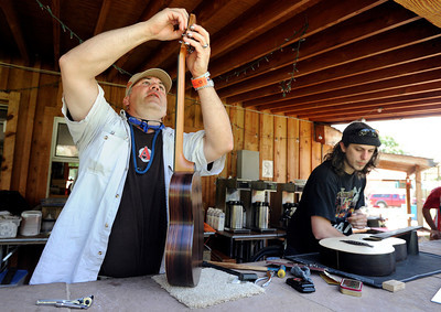 Jim Burrus, of Longmont, left, and Chris Jonaitis, of Boulder, work to finish building their own custom instruments on Thursday, July 26, at the Rocky Grass Academy in Lyons. For more photos and video of the academy go to www.dailycamera.com Jeremy Papasso/ Camera