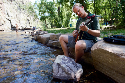 Kerry Grimes, of Lyons, plays his mandolin by the river on Thursday, July 26, at the Rocky Grass Academy in Lyons. For more photos and video of the academy go to www.dailycamera.com Jeremy Papasso/ Camera