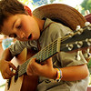 "Waylen Perkins, 10, of St. George, Utah, jams away on the guitar while sitting under a tent at the Rocky Mountain Folks Festival on Friday, Aug. 13, at the Planet Bluegrass Ranch in Lyons.<br /> Jeremy Papasso/ Camera<br /> <br /> For photo gallery and video go to  <a href=""http://www.dailycamera.com"">http://www.dailycamera.com</a>"