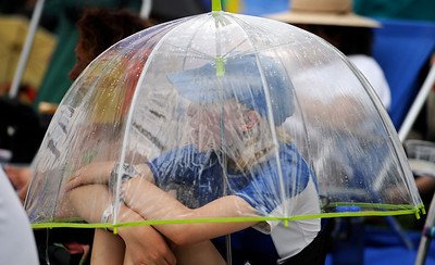 A brief rain causes Lara Lufkin, 14, to tuck under an umbrella at the Rocky Mountain Folks Festival in Lyon, Colorado August 19, 2011.   CAMERA/Mark Leffingwell