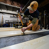 KRISTOPHER RADDER — BRATTLEBORO REFORMER<br /> Greg Durocher, owner of Roll'en Homes, in Townshend, Vt., uses a nail gun to tack the flooring down to the trailer on a tiny house that he is working on.