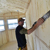 KRISTOPHER RADDER — BRATTLEBORO REFORMER<br /> Greg Durocher, owner of Roll'en Homes, in Townshend, Vt., uses a saw to cut the foam insulation flush with the studs on a tiny house.