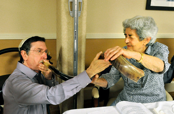Jerry Sloat, left, blows the shofar for Renate Alpert to feel the vibrations of the noise during a Rosh Hashanah service at the Boulder Meridian in Boulder, Colorado Thursday September 13, 2012. Alpert, who is deaf, couldn't hear the sound of the traditional ram's horn which is blown during the Jewish holiday, Rosh Hashanah, which is the Jewish New Year, and the first of the High Holy Days. DAILY CAMERA/ JESSICA CUNEO