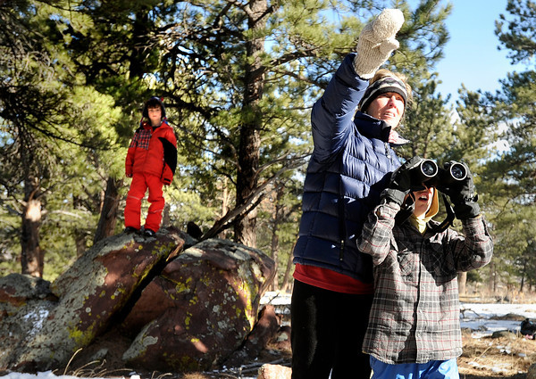"Running River School Director Nancy Monson points to a ridge while second grader Zorba Abraxus looks through his binoculars during a school hike on Friday, Jan. 13, at the Shanahan Ridge Trail in Boulder. Third grade student Owen Hinrichs, left, was watching from a distance. For a video of the hike go to  <a href=""http://www.dailycamera.com"">http://www.dailycamera.com</a><br />  Jeremy Papasso/ Camera"