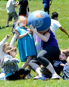 Fourth grade teacher Molly Hayes falls on top of first grader Tyler Price after making a catch during a kickball game on Thursday, May 24, at Ryan Elementary School in Lafayette. For more photos and video of the 5th grade vs. the teachers kickball game go to www.dailycamera.com Jeremy Papasso/ Boulder Daily Camera