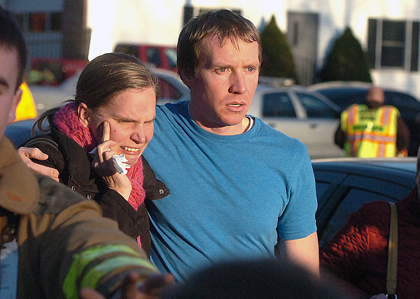 People leave the Sandy Hook Volunteer Fire House in tears after a shooting at the Sandy Hook Elementary School, Friday morning, Dec. 14, 2012 in Newtown, Conn. A man opened fire Friday inside two classrooms at the Connecticut elementary school where his mother was a teacher, killing 26 people, including 20 children, as youngsters cowered in corners and closets and trembled helplessly to the sound of shots reverberating through the building. (AP Photo/The Hour, Alex von Kleydorff)