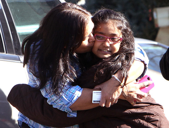 A woman hugs her daughter after being reunited at the Sandy Hook firehouse after a mass shooting at the Sandy Hook Elementary School in Newtown, Conn. on Friday, Dec. 14, 2012. (AP Photo/The Journal News, Frank Becerra Jr.) NYC OUT, NO SALES, TV OUT, NEWSDAY OUT; MAGS OUT; MANDATORY CREDIT: THE JOURNAL NEWS, FRANK BECERRA JR.