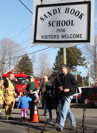 Parents walk past police and firefighters away from the Sandy Hook Elementary School with their children following a shooting at the school, Friday, Dec. 14, 2012 in Newtown, Conn. A man opened fire inside the Connecticut elementary school where his mother worked Friday, killing 26 people, including 20 children, and forcing students to cower in classrooms and then flee with the help of teachers and police. (AP Photo/The Journal News, Frank Becerra Jr.) MANDATORY CREDIT, NYC OUT, NO SALES, TV OUT, NEWSDAY OUT; MAGS OUT
