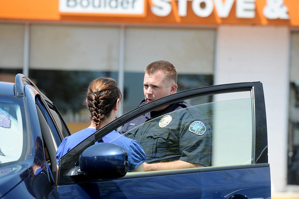 A police officer talks with a person at the scene of a reported shooting Monday morning at Boulder Stove and Floor in Boulder.<br /> Photo by Marty Caivano / The Boulder Camera