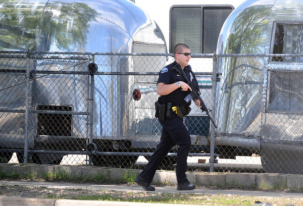 An armed police officer searches the scene of a reported shooting Monday morning at Boulder Stove and Floor in Boulder.<br /> Photo by Marty Caivano / The Boulder Camera
