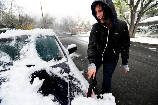 Ellie Grove takes a moment to clear the snow from her car in Boulder on her way to school at the Southwest Acupuncture College on Tuesday April 3, 2012 <br /> Photo by Paul Aiken / The Camera