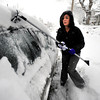 Amanda Fransen clears her car of snow in Boulder on Thursday morning. <br /> Photo by Paul Aiken The Camera