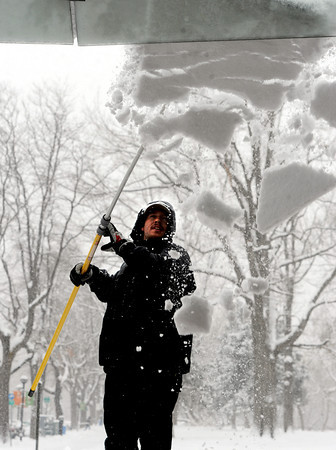 """Stephen Hacker removes  snow from the awning at the UBS building off of Canyon Blvd. on Sunday.<br />  For more photos and a video of the current storm, go to  <a href=""""http://www.dailycamera.com"""">http://www.dailycamera.com</a>. <br />  Cliff Grassmick  / February 24, 2013"""