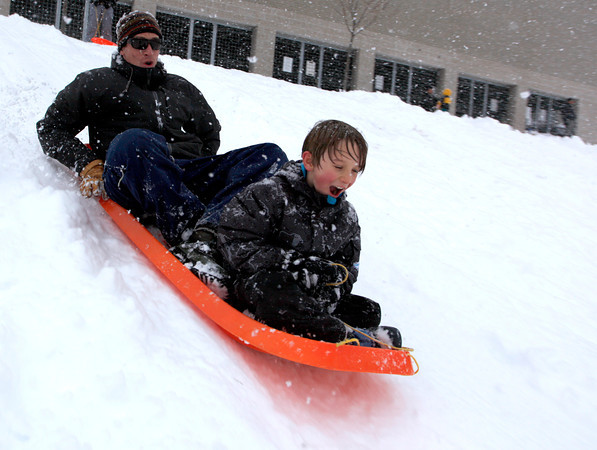 Eric Lyon, left,  and his son Banyon Lyon, 7, right, sleds down the hill behind Casey Middle School, Feb. 3, 2011, Boulder.<br /> <br /> Photo By Derek Broussard