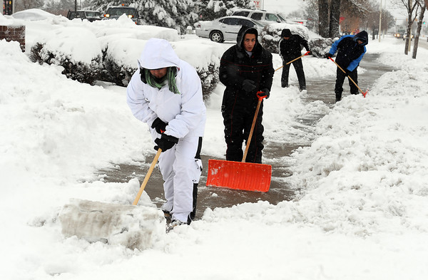 """Oscar Cortez, left, leads a group of workers clearing the sidewalks along Ken Pratt  Blvd in Longmont Friday morning.<br /> For more photos of the snow, go to  <a href=""""http://www.dailycamera.com"""">http://www.dailycamera.com</a>.<br /> February 3, 2012 / Cliff Grassmick"""