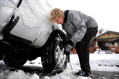 Scott Thompson works to put chains on to free his car from his parking spot in Boulder.  He was on his way to work delivering pizzas.  Photo by Paul Aiken / The Camera