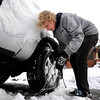 Scott Thompson works to put chains on to free his car from his parking spot in Boulder.  He was on his way to work delivering pizzas. <br /> Photo by Paul Aiken / The Camera
