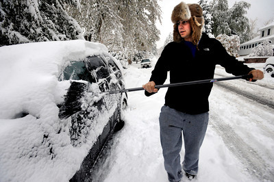 Andrew Wax clears his car of snow on Wednesday morning on University Hill in Boulder. Photo by Paul Aiken / The Camera