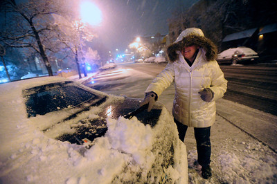 SNOW.JPG SNOW Angelique Espinoza clears snow from her car in downtown Boulder on Tuesday night.  PHOTO BY MARTY CAIVANO Nov. 1, 2011