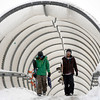 Looking for a place to build a snowboard ramp, Jimmy Spindler (left) and Brian Hair (right) cross the snow covered pedestrian bridge over Foothills Parkway after last nights snow storm in Boulder, Colorado November 2, 2011.  CAMERA/Mark Leffingwell