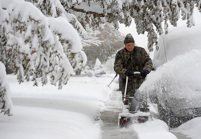 Gene Varra uses his snow blower to clear the sidewalks in his neighborhood and get some exercise after last nights snow storm in Louisville, Colorado November 2, 2011.  CAMERA/Mark Leffingwell
