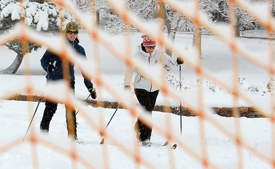 Laura Freeman, left, and Molly Higginbottom are seen skiing through a fence at North Boulder Park. For more photos of the snow, go to www.dailycamera.com. Cliff Grassmick / November 2, 2011