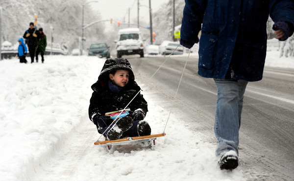 Bryan Kofler, 4 gets a pull from his mom Jennifer on his way to preschool Wednesday on University Hill in Boulder.<br /> Photo by Paul Aiken / The Camera