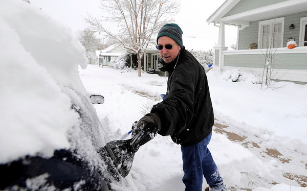 Steven Moss clears snow from his car after last nights snow storm in Louisville, Colorado November 2, 2011.  CAMERA/Mark Leffingwell