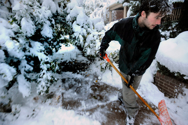 Neil Chelton of Trident snow removal works around a snow heavy tree that has blocked a sidewalk in Boulder on Wednesday morning<br /> Photo by Paul Aiken