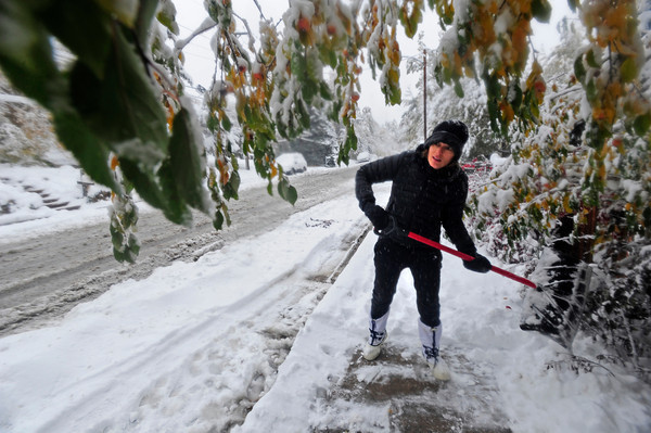 SNOW<br /> Leah Csapo shovels the walk in front of her house, which also has no power, in Boulder on Wednesday.<br /> PHOTO BY MARTY CAIVANO<br /> OCT.26, 2011