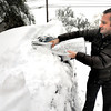 Scott Roberts uses his summer sun shade to try to clear the snow from his car  in Boulder on Wednesday morning. He gave up and went back inside his house to find a real snow scraper.<br /> Photo by Paul Aiken