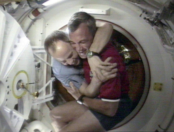 FILE - In this Saturday, Jan. 24, 1998 image made from video provided by NASA, Shuttle Commander Terrence Wilcutt, right, and Mir Commander Anatoly Solovyev, left, hug after opening the hatches between the space shuttle Endeavour and the Russian space station Mir. (AP Photo/NASA)