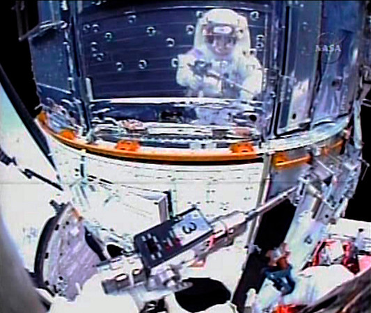 FILE - In this Monday, May 18, 2009 image made from video provided by NASA, astronaut John Grunsfeld is reflected on the surface of the Hubble Space Telescope as he works to upgrade the orbiting observatory during a spacewalk on the fifth and final repair mission for the then 19-year-old telescope. (AP Photo/NASA TV)