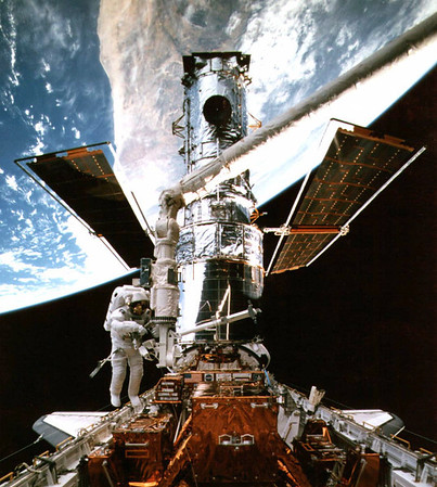 FILE - In this Feb. 15, 1997 picture provided by NASA, astronaut Steven Smith works at the end of the space shuttle's remote manipulator system as he performs maintenance on the Hubble Space Telescope during a space walk. In the background is a portion of Australia along the Earth's curve. (AP Photo/NASA/file)