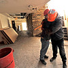 "St. Malo's operations manager Jeff Rivar hugs the center's director, Jose Ambrozic, at the center on Tuesday. Ambrozic lost all of his personal belongings when the center's main lodge caught fire on Nov. 14. ""Sometimes God wants us to travel lighter,"" said Ambrozic. <br /> Photo by Walt Hester 