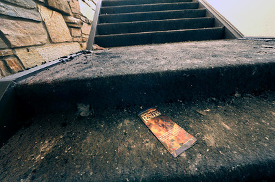 A brochure lies on a step amidst ashes and dirt at the St. Malo Retreat near Allenspark on Tuesday. Crews are cleaning up and shoring up the structure before engeneers determine how much of the structure can be saved. For more photos go to www.dailycamera.com Photo by Walt Hester | Trail Gazette