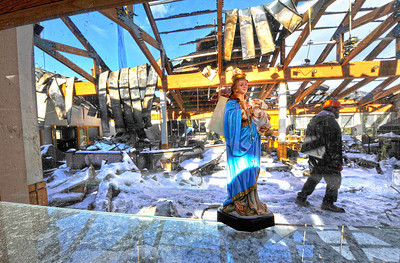 A statue of the Virgin Mary leans on a window in the St. Malo gift shop as operations manager Jeff Rivard surveys the damage at the retreat on Tuesday. While many suspect the fireplace in the room to be the origin of the fire, no official cause has been given for the November 14 fire. For more photos go to www.dailycamera.com Photo by Walt Hester | Trail Gazette
