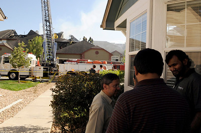 Hadi Hashmi, at right, talks to some friends while firefighters work to put out a structure fire at the Summit Condominiums building at 2855 Rock Creek Circle in Superior. Hashmi's condominium was one of the units that were destroyed in the fire. Hashmi's 13-year-old daughter was babysitting her 2-year-old sister and was able to call 911 and evacuate before anyone was seriously injured. Jeremy Papasso/ Camera