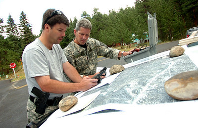 Sergeant Bill Crist, left, and Brendan Beggans check maps and equipment  as they prepare move into the mountains in Raymond Colorado on Monday August 30, 2010. They were acting on a report of a marijuana growing facility in the forest near the town Photo by Paul Aiken /  August 30, 2010.