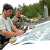 Sergeant Bill Crist, left, and Brendan Beggans check maps and equipment  as they prepare move into the mountains in Raymond Colorado on Monday August 30, 2010. They were acting on a report of a marijuana growing facility in the forest near the town<br /> Photo by Paul Aiken /  August 30, 2010.