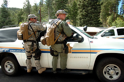 SWAT team members ride on the outside of a BCSO vehicle  as they prepare move into the mountains in Raymond Colorado on Monday August 30, 2010. They were acting on a report of a marijuana growing facility in the forest near the town Photo by Paul Aiken /  August 30, 2010.