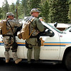 SWAT team members ride on the outside of a BCSO vehicle  as they prepare move into the mountains in Raymond Colorado on Monday August 30, 2010. They were acting on a report of a marijuana growing facility in the forest near the town<br /> Photo by Paul Aiken /  August 30, 2010.
