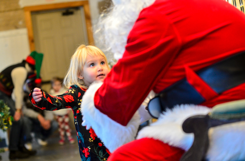 KRISTOPHER RADDER — BRATTLEBORO REFORMER<br /> Persephone Sanborn, 2, lights up as she opens her arms to give a hug to Santa Claus.
