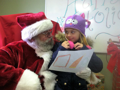BOB SANDRICK / GAZETTE Brooke Pinkerton, 7, of Wadsworth was just a little shy with Santa on Saturday morning at Wadsworth Municipal Airport. Brooke's mom Jennifer Pinkerton accompanied her.