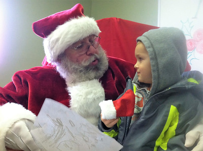 BOB SANDRICK / GAZETTE Mason Mangan, 3, of Spencer told Santa what he wanted for Christmas on Saturday morning at Wadsworth Municipal Airport. Mason's mom Elizabeth was also there.