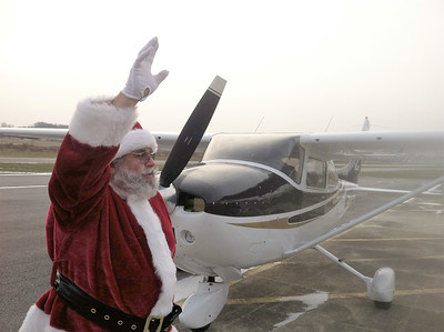 BOB SANDRICK / GAZETTE Santa waves to his fans Saturday after arriving at Wadsworth Municipal Airport.